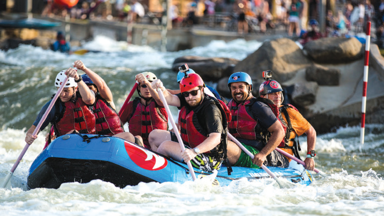 five people in a raft at U.S. National Whitewater Center