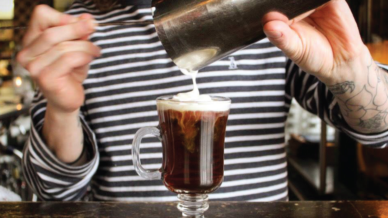 Irish coffee from merchant being poured in a glass by a bartender