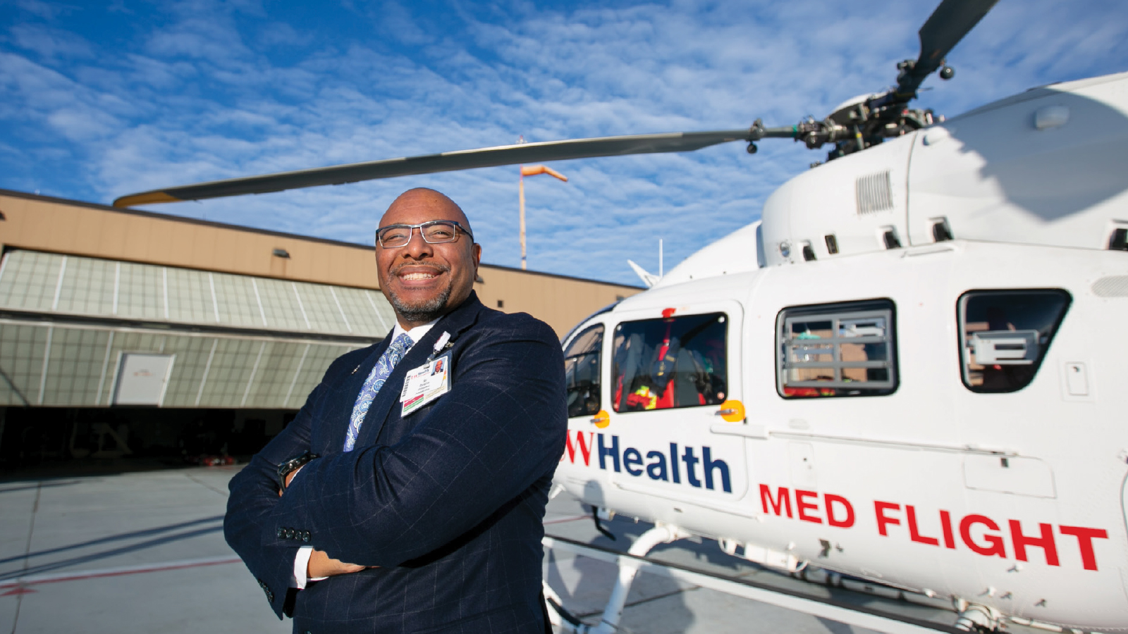 Ric Ransom standing on the roof of UW Hospital with a Med Flight helicopter