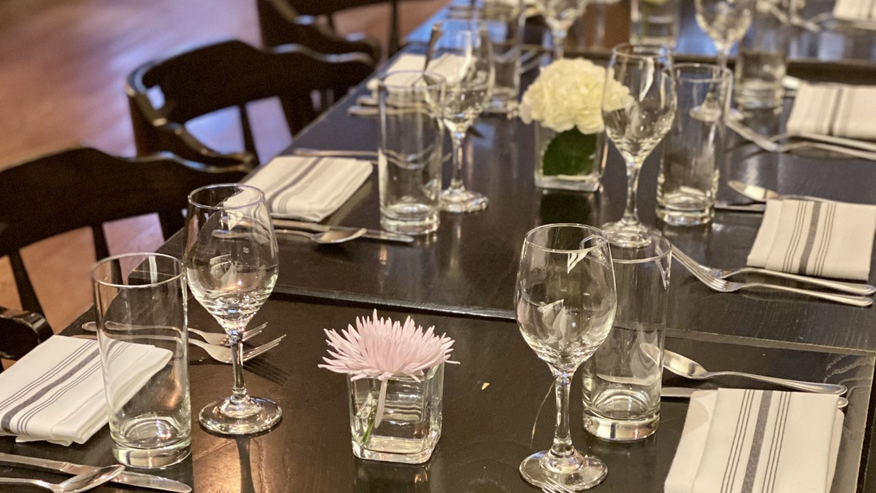 Wine glasses, napkins, flowers, plates and silverware set on a table.