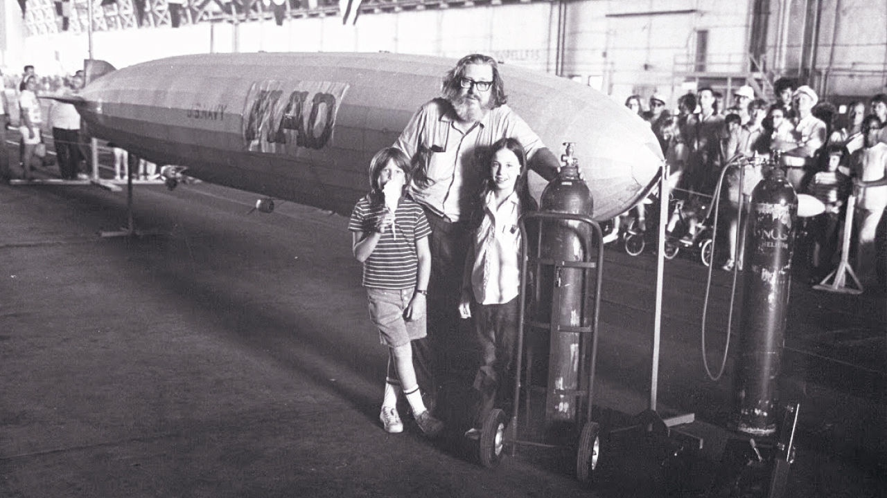 William M. Gaines stands with his children Chris and Wendy in front of a small blimp with his magazine's name on it at the Lakehurst Naval Air Station in Lakehurst, New Jersey, in 1970.