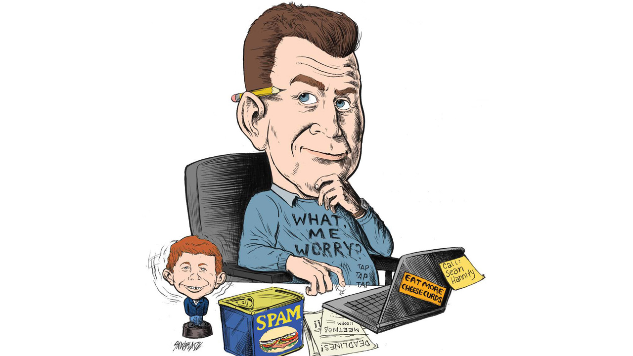 """John Roach sitting in a chair with a """"What me worry?"""" shirt and an Alfred E. Neuman bobblehead"""