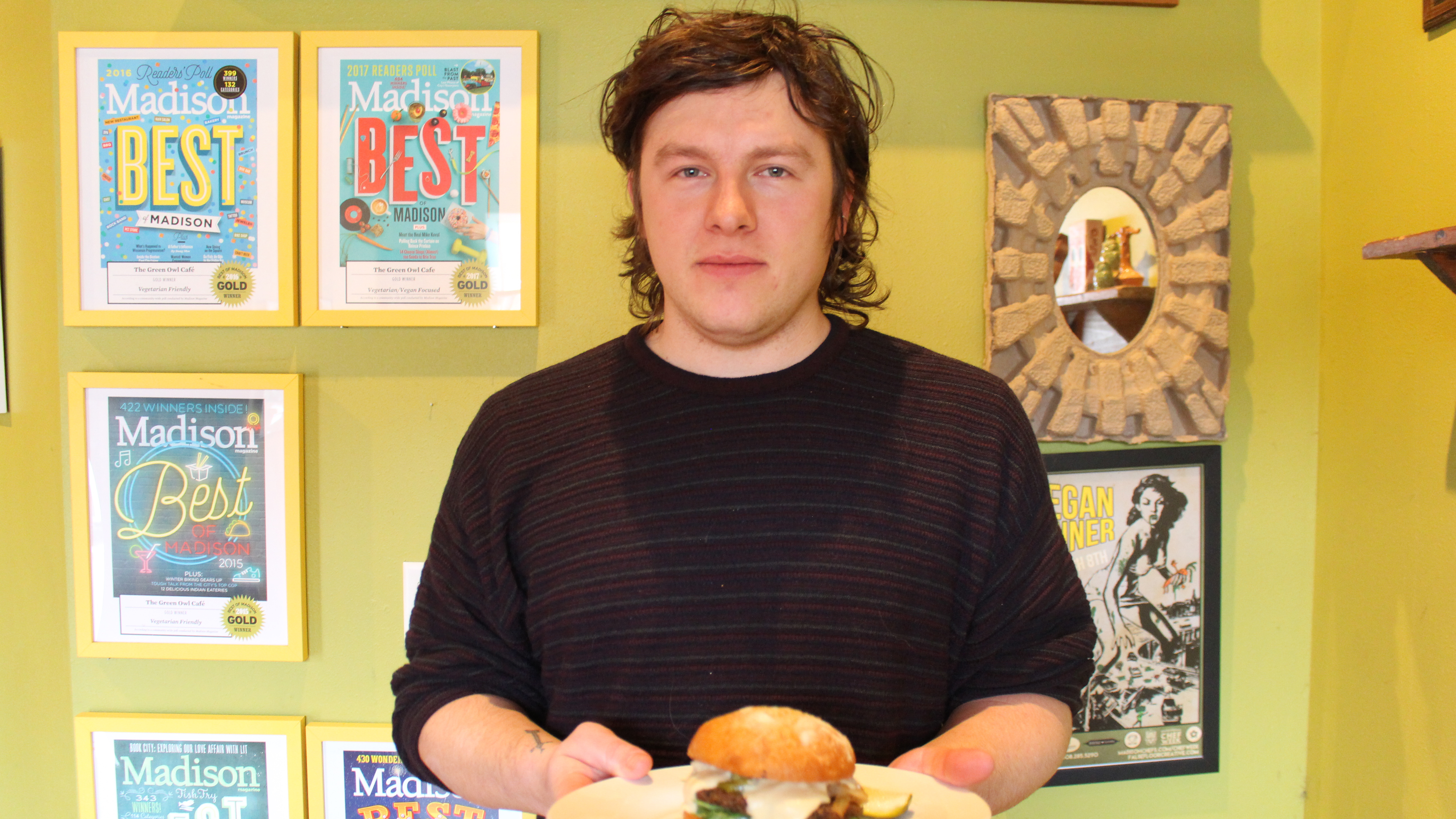 Erick Fruehling standing in The Green Owl Cafe with a burger