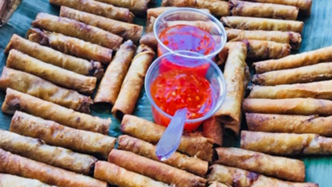 Filipino eggrolls on a blue platter with a bowl of red sauce.