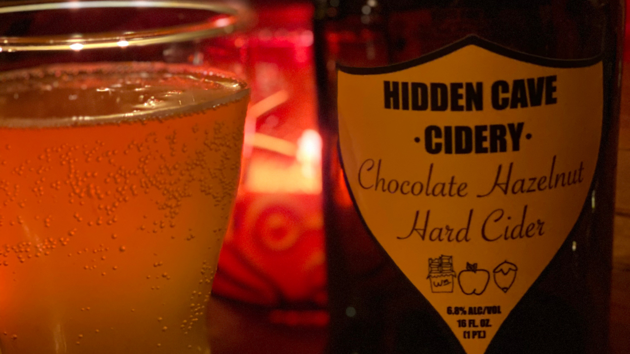 """Cider in a glass next to bottle labeled """"Hidden Cave Cidery"""""""