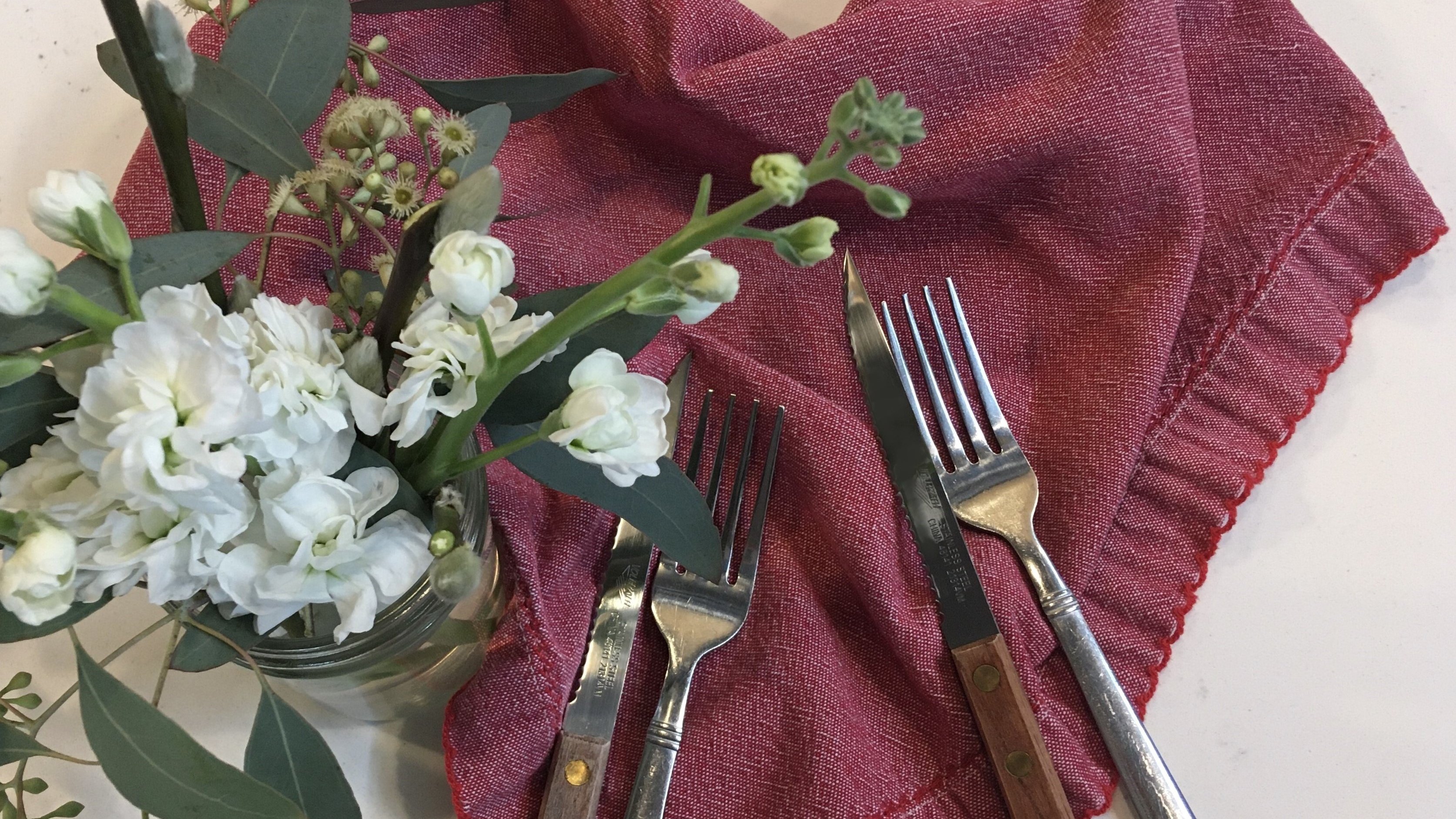 Place setting with red napkin, silverware and white flowers