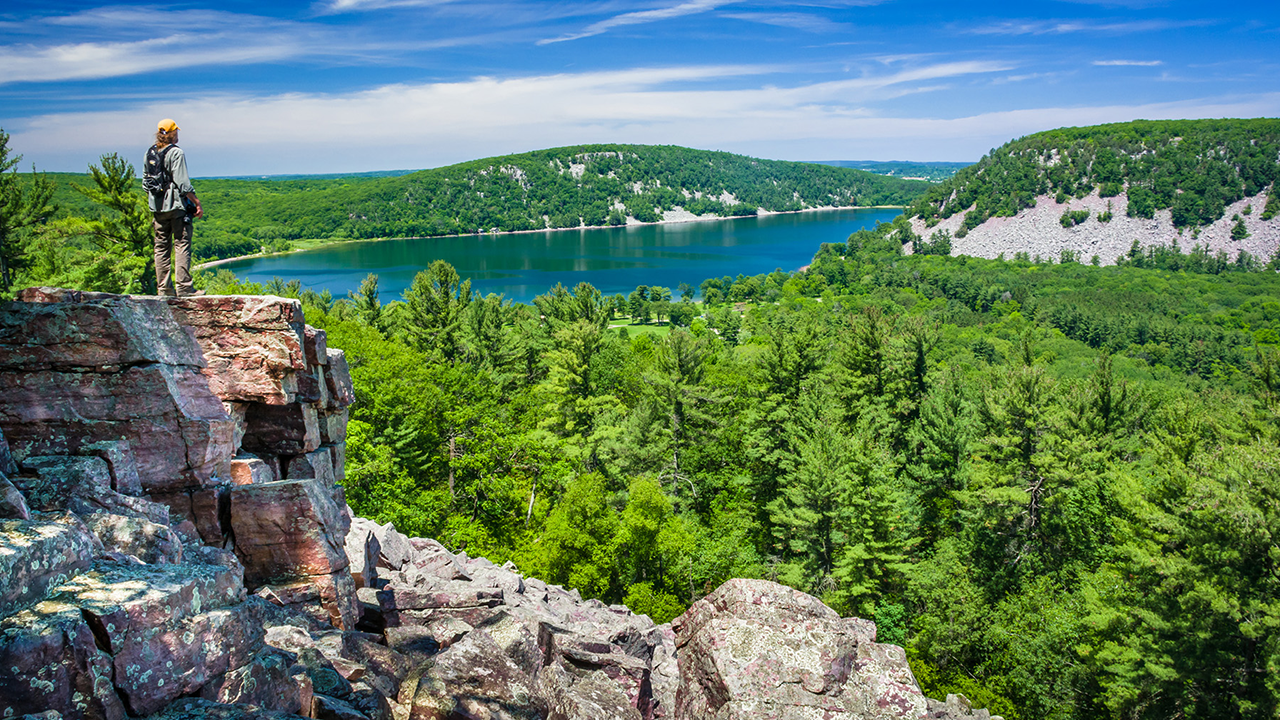 A man stands on a ledge overlooking Devil's Lake State Park