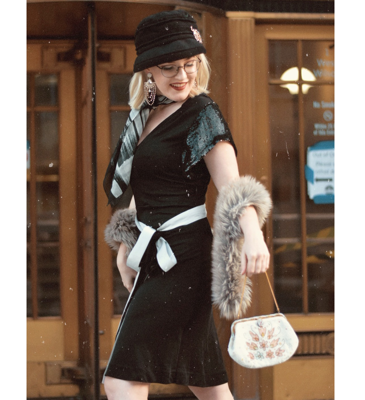 Blonde woman in a black 1920s-themed dress holding a beaded purse with a fur stole around her forearm