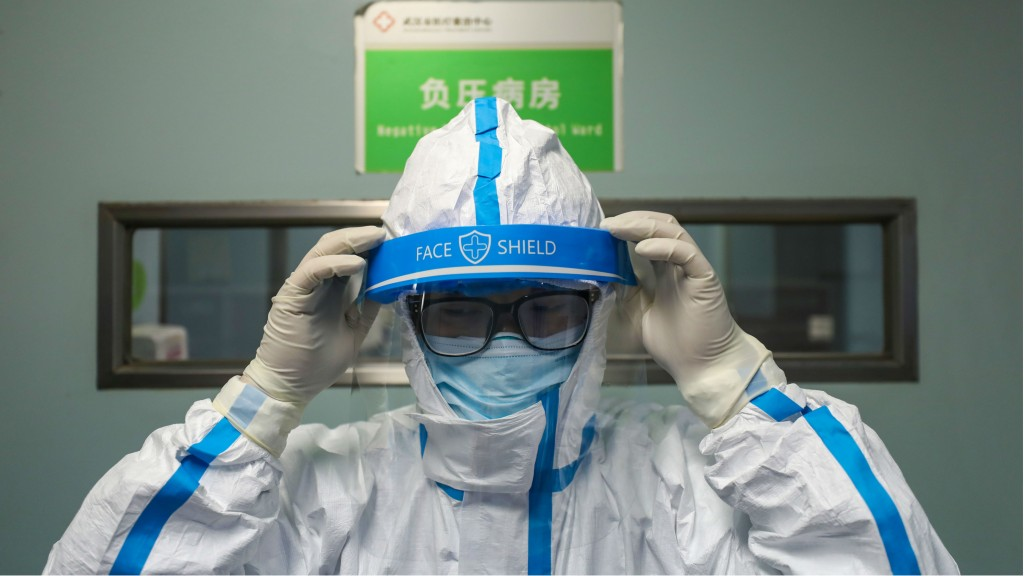 A doctor puts on the isolation outfit before entering the negative-pressure isolation ward in Jinyintan Hospital in Wuhan.