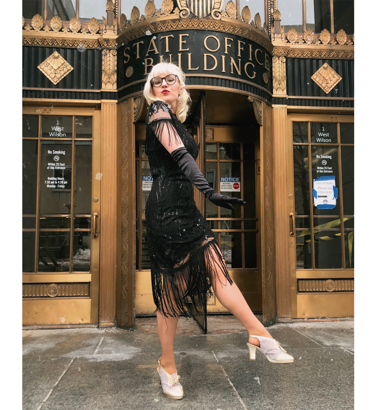 Blonde woman striking a pose in a flapper dress outside of the state office building