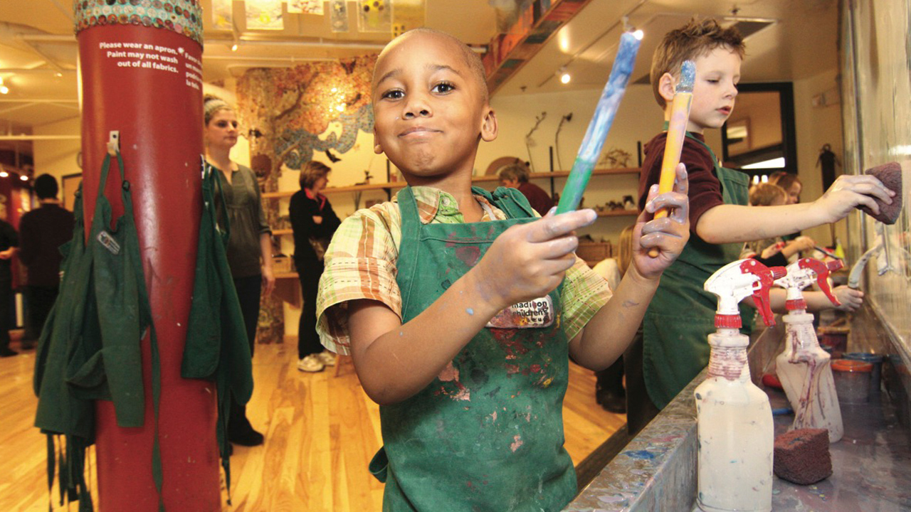 A happy little boy in an apron holding a paint stick at the Madison Childrens Museum