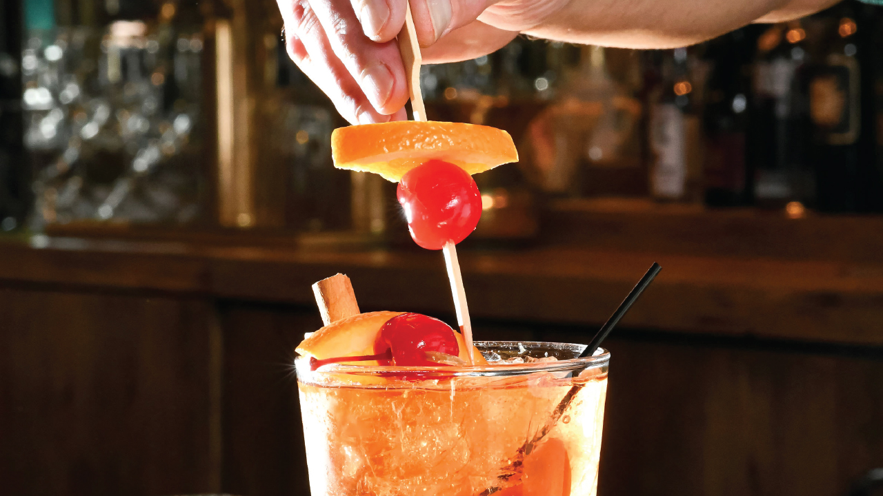 person putting in a garnish of an Old-Fashioned cocktail