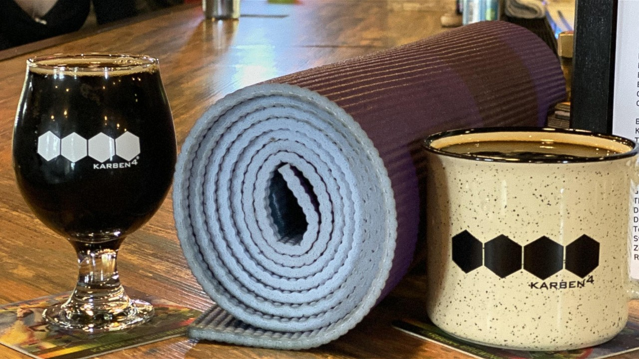 A glass of beer, a yoga mat and a mug on a countertop