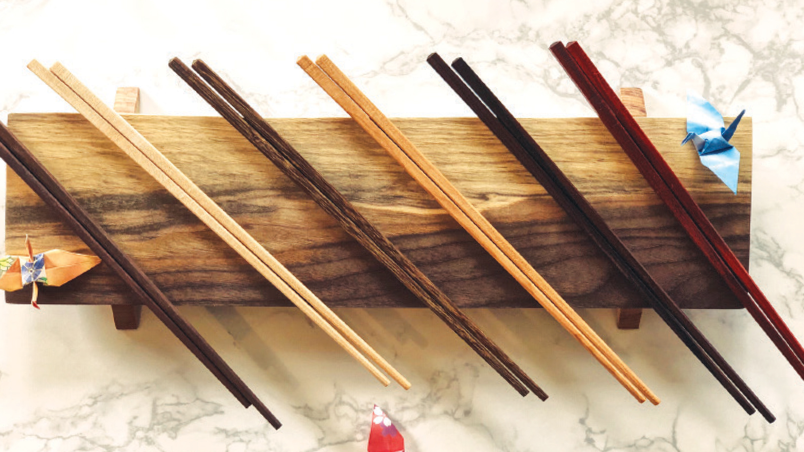 six pairs of chopsticks on a piece of wood