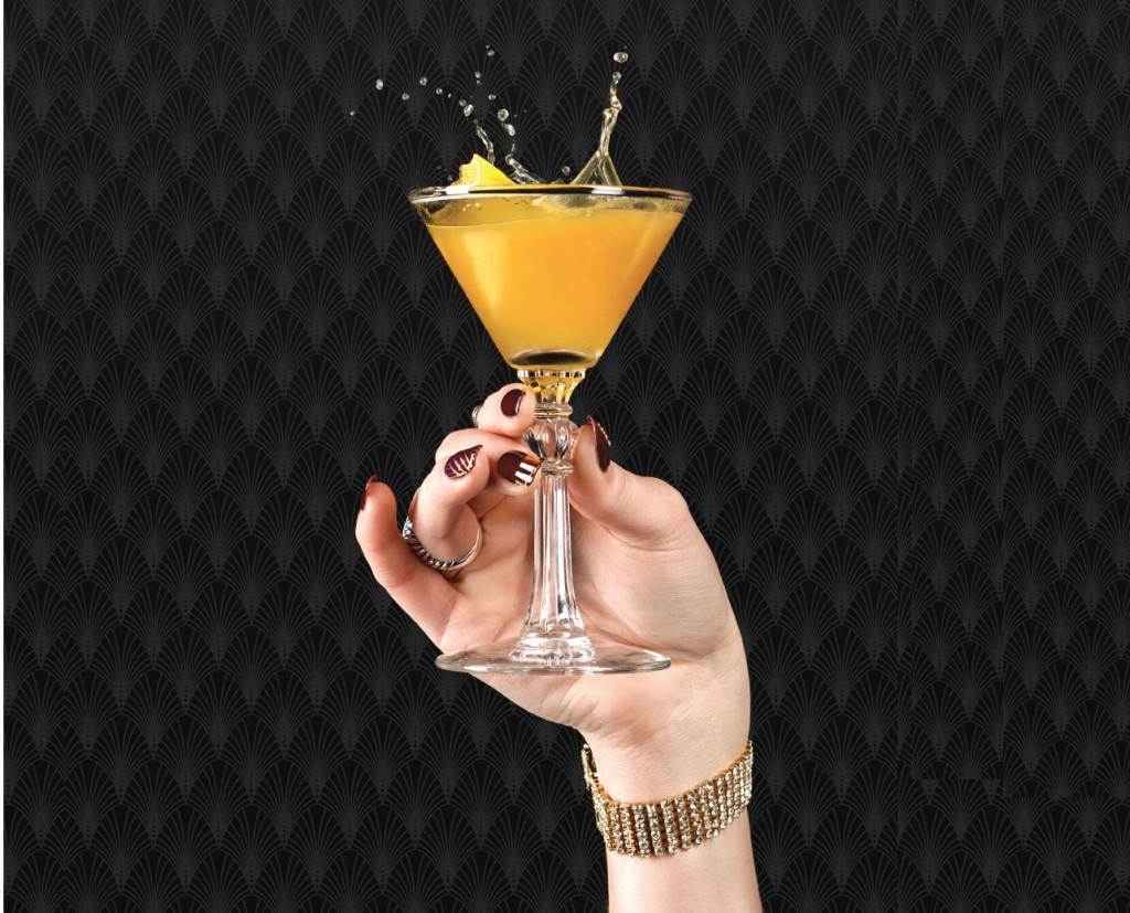 yellow cocktail being held in her hand