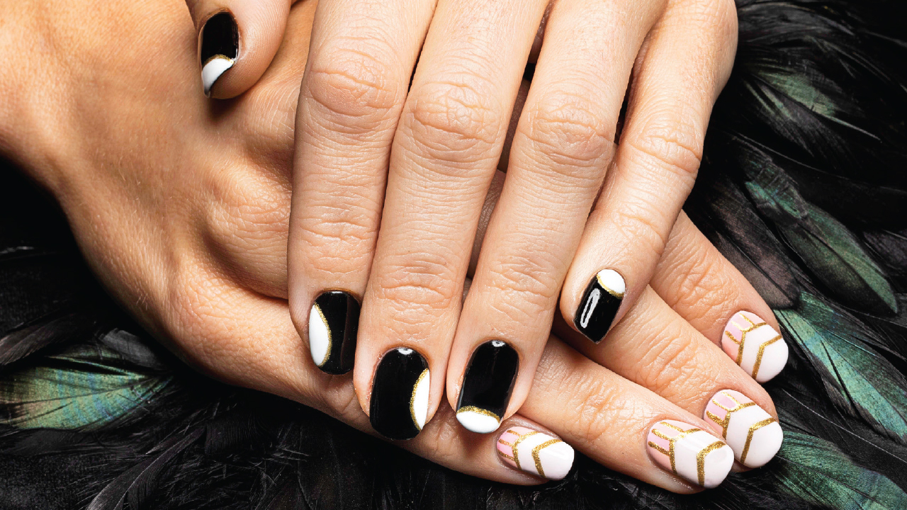 two hands with decorated nails