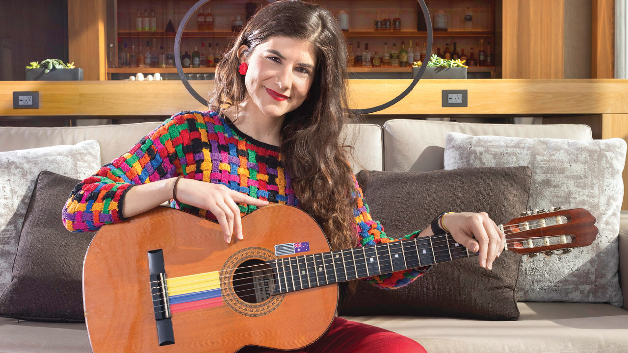 Angela Puerta on a couch with her guitar