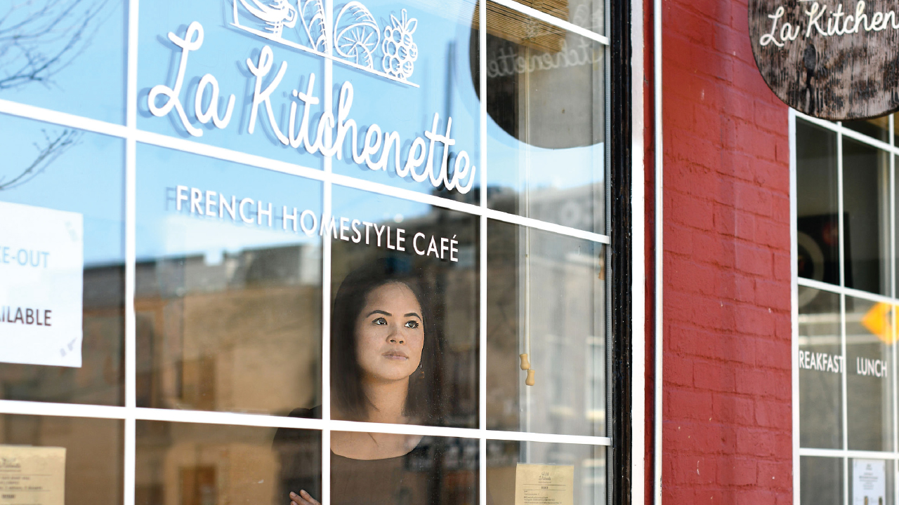 Virginie Ok staring out of a window at La Kitchenette