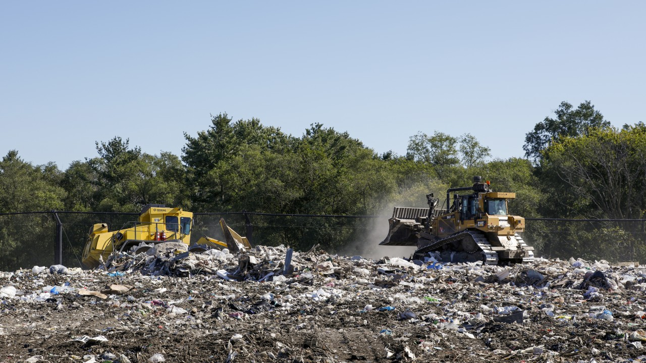 Two construction vehicles over the landfill