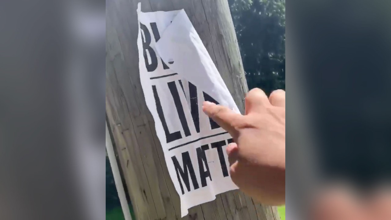 A screengrab from a video in which a far-right group member rips a Black Lives Matter poster from a tree