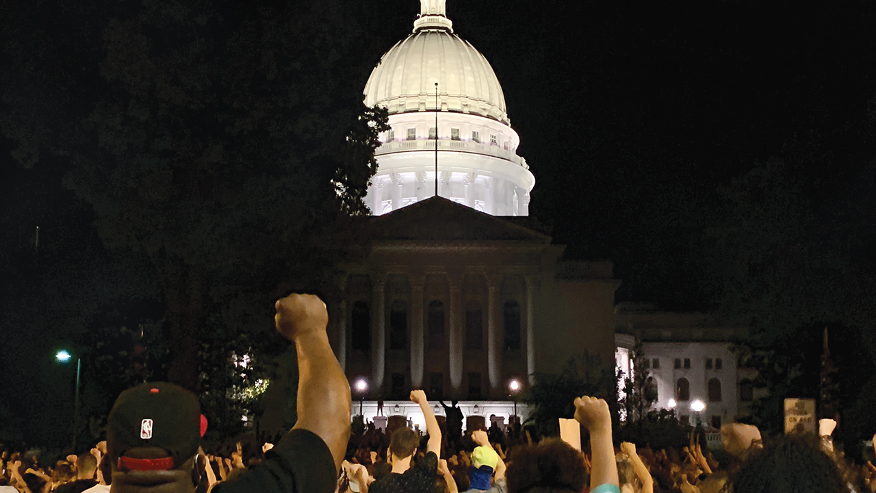 people hold up their fists in front of State Capitol