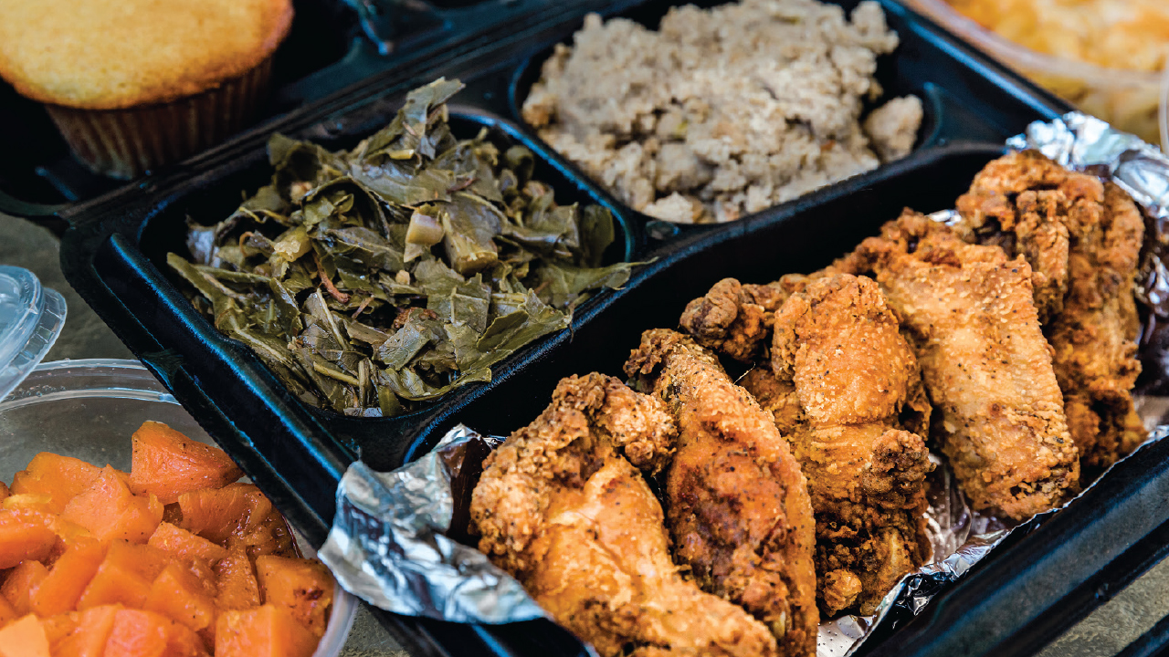 takeout container with collard greens and chicken wings