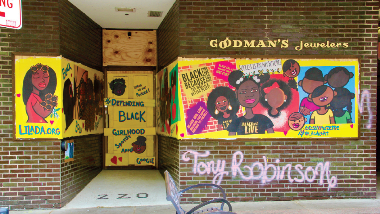 Murals on the Goodman's Jewelrs that have black girls and lines that say defending Black girlhood