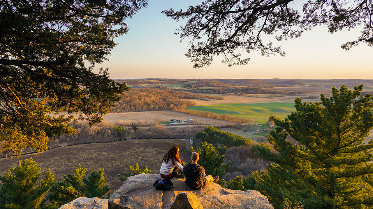 two individuals sitting on a rock overlooking fields