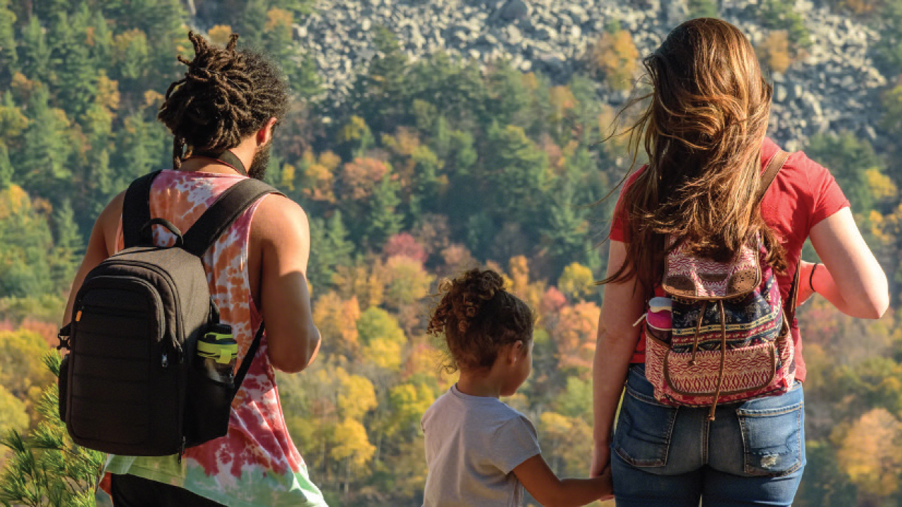 three individuals, one a small child, overlooking a bluff with trees
