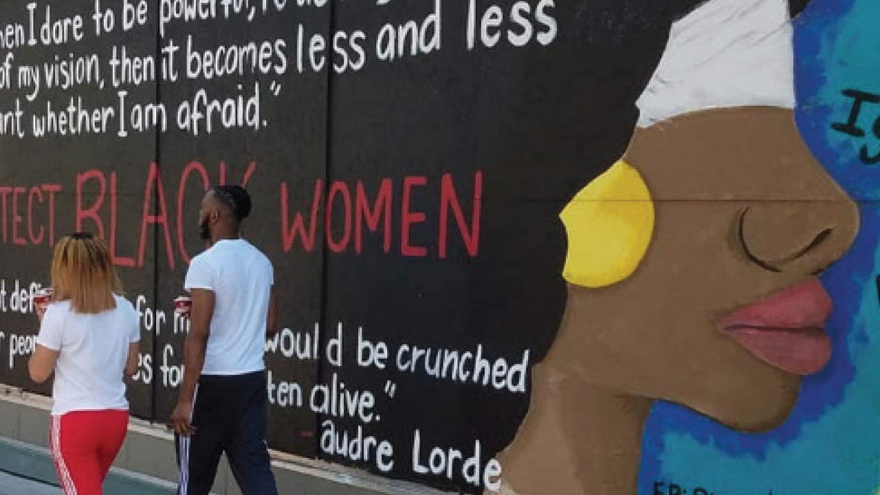 Mural featuring a Black woman's face and a quote that says Protect Black Woman