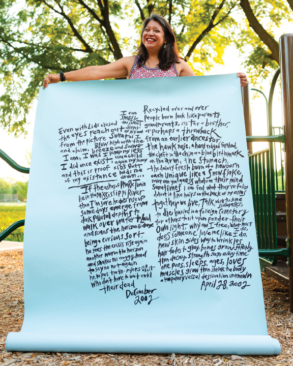 Angela holding a massive sheet of paper with her poems