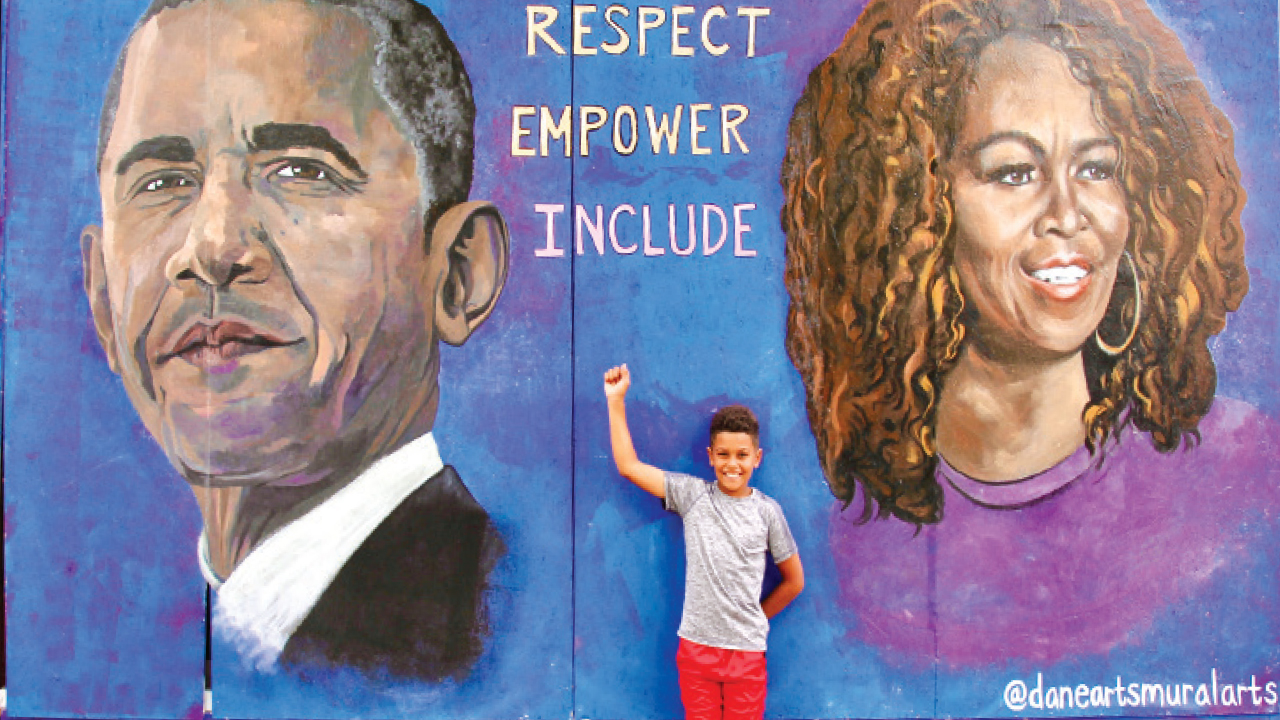 Barack Obama and Michelle Obama mural with a little boy standing in front of it with a fist up