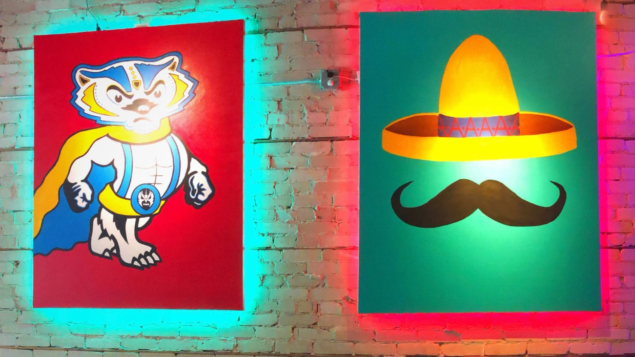 Two neon signs in Luchador Madison's new state street location are hung on a brick wall, one of Bucky the Badger and another of a hat over a mustache.