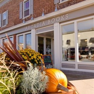 Arcadia Books storefront, partially obscured by fall decorations including a pumpkin, in Spring Green, WI.
