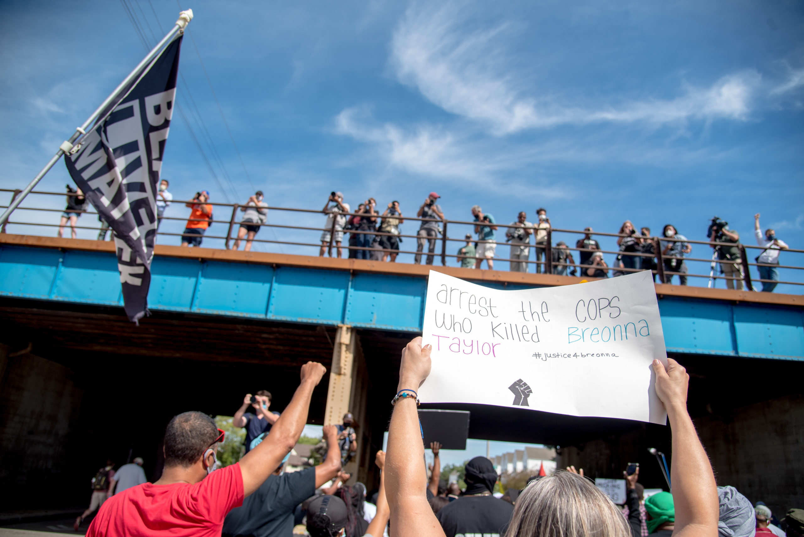 Photographers and press look down from a railroad bridge at a march in Kenosha, Wis. on Aug. 29, 2020, demanding justice for Jacob Blake, a Black man shot in the back seven times by Kenosha police.