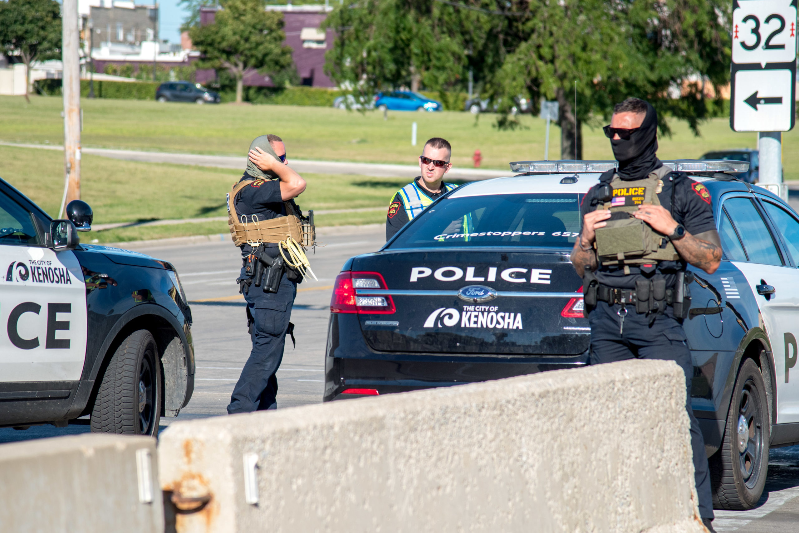 Kenosha, Wis., police officers are seen near the edge of a rally calling for justice for Jacob Blake, a Black man who was shot seven times in the back by a Kenosha police officer . Photographed on Aug. 29, 2020.