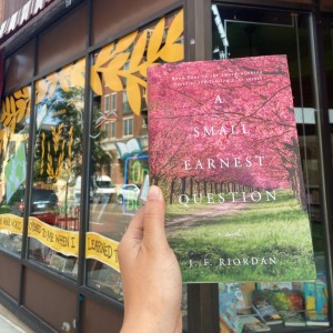 """""""A Small Earnest Question,"""" a book by a local Wisconsin author, is held in front of Mystery to Me's storefront windows."""