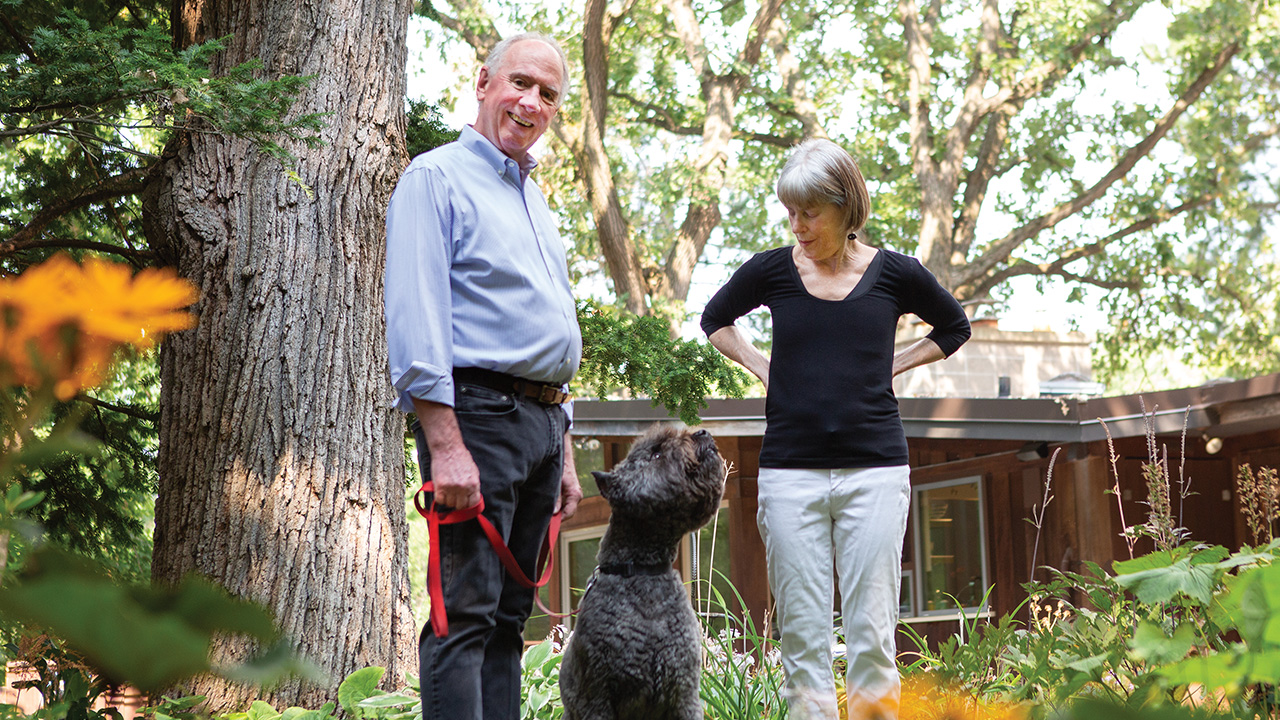 Neil Heinen and his wife, Nancy Christy, stand in their backyard along with their dog, Macaroon, who is a bouvier des Flandres.