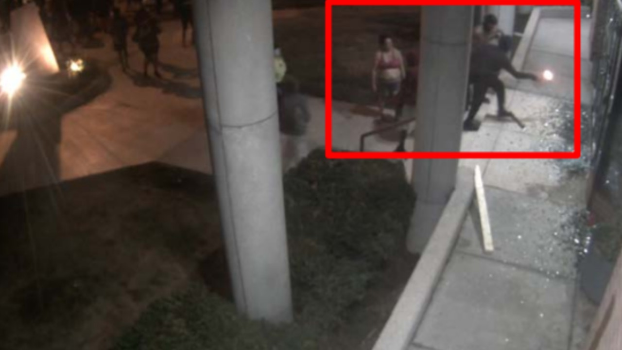 Wide-shot surveillance image shows person igniting flammable liquid, vapors