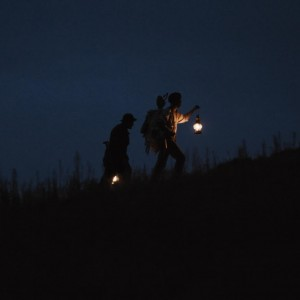 The silhouettes of two men carrying lanterns are just visible above a hilltop.