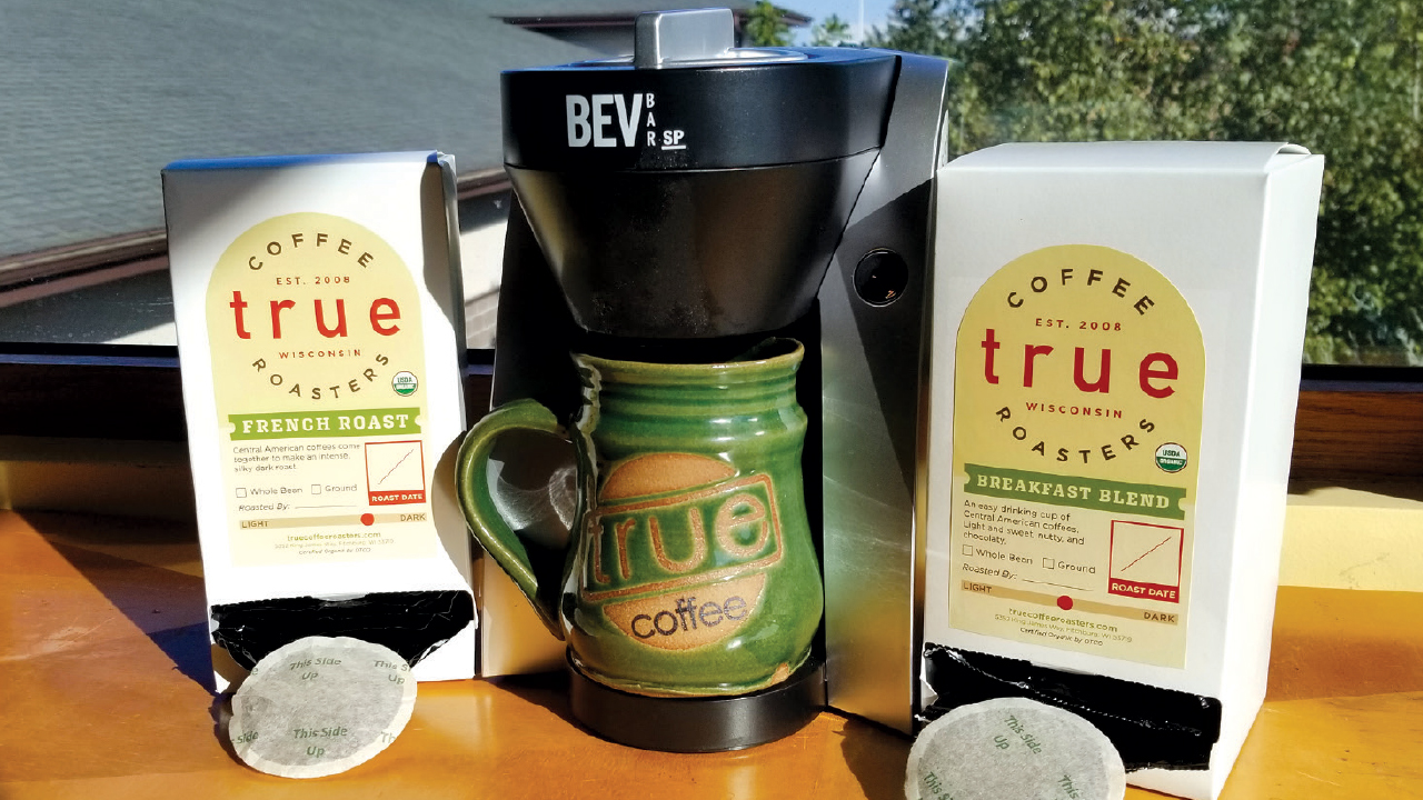 compostable k-cups next to a coffee maker