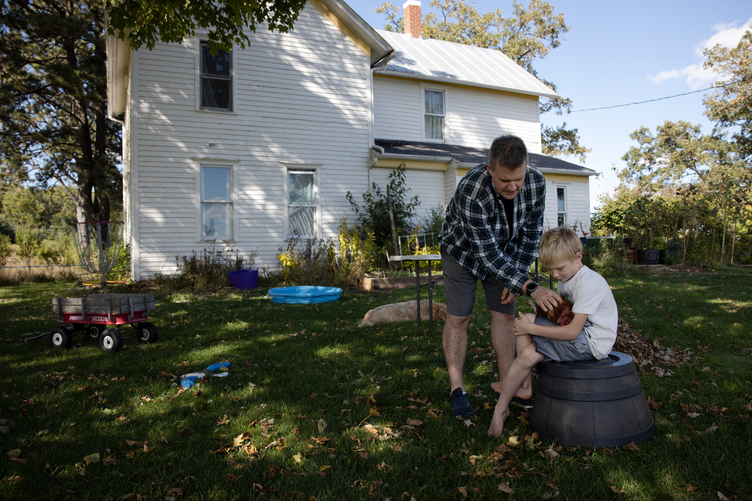 Matt Millar is seen with his son Sterling, 7, outside his house in Blue Mounds, Wis., on Sept. 18, 2020. To give his children a break from online schooling, Millar says he organized games in the yard including catching chickens.