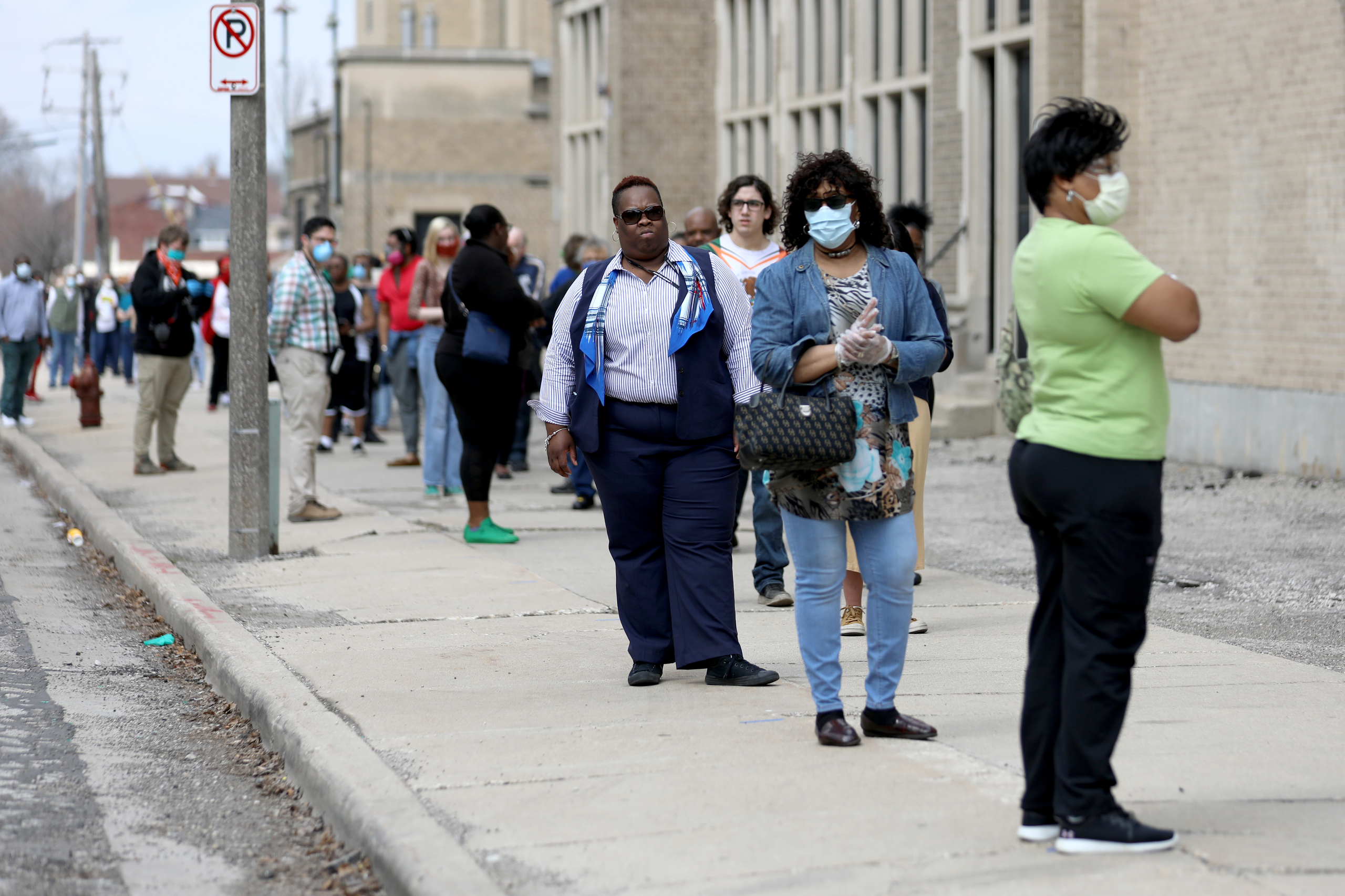 """A line of voters wraps around the block outside Washington High School in Milwaukee during the primary election on April 7, 2020. A top civil rights advocate called Wisconsin's election a """"travesty that put voters in the crosshairs of having to choose between their safety and their vote."""" Various lawsuits are seeking a relaxation of Wisconsin's voting laws ahead of the Nov. 3 election due to the pandemic."""