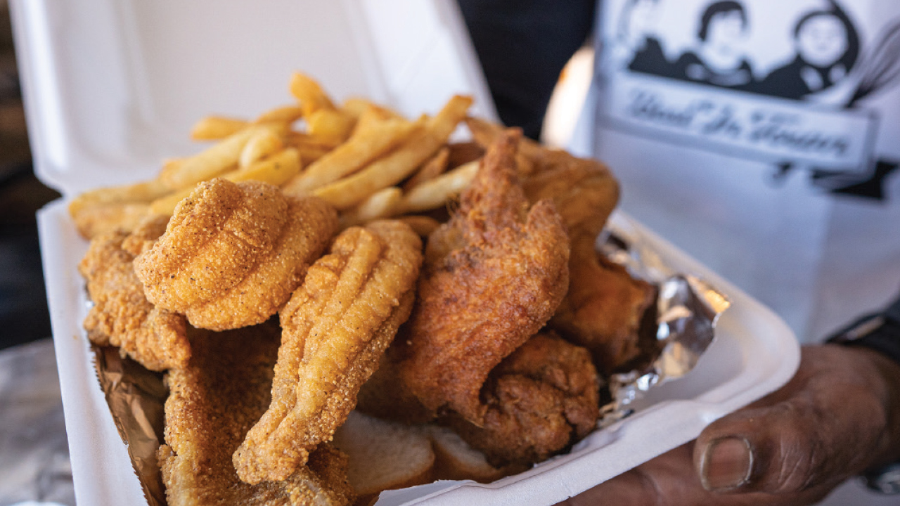 fried catfish and chicken with fries in a to-go box