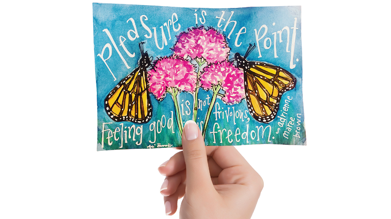 person holding postcard that has flowers and butterflies