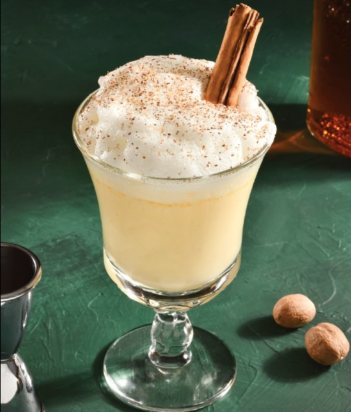 Egg Nog in a glass with a cinnamon stick