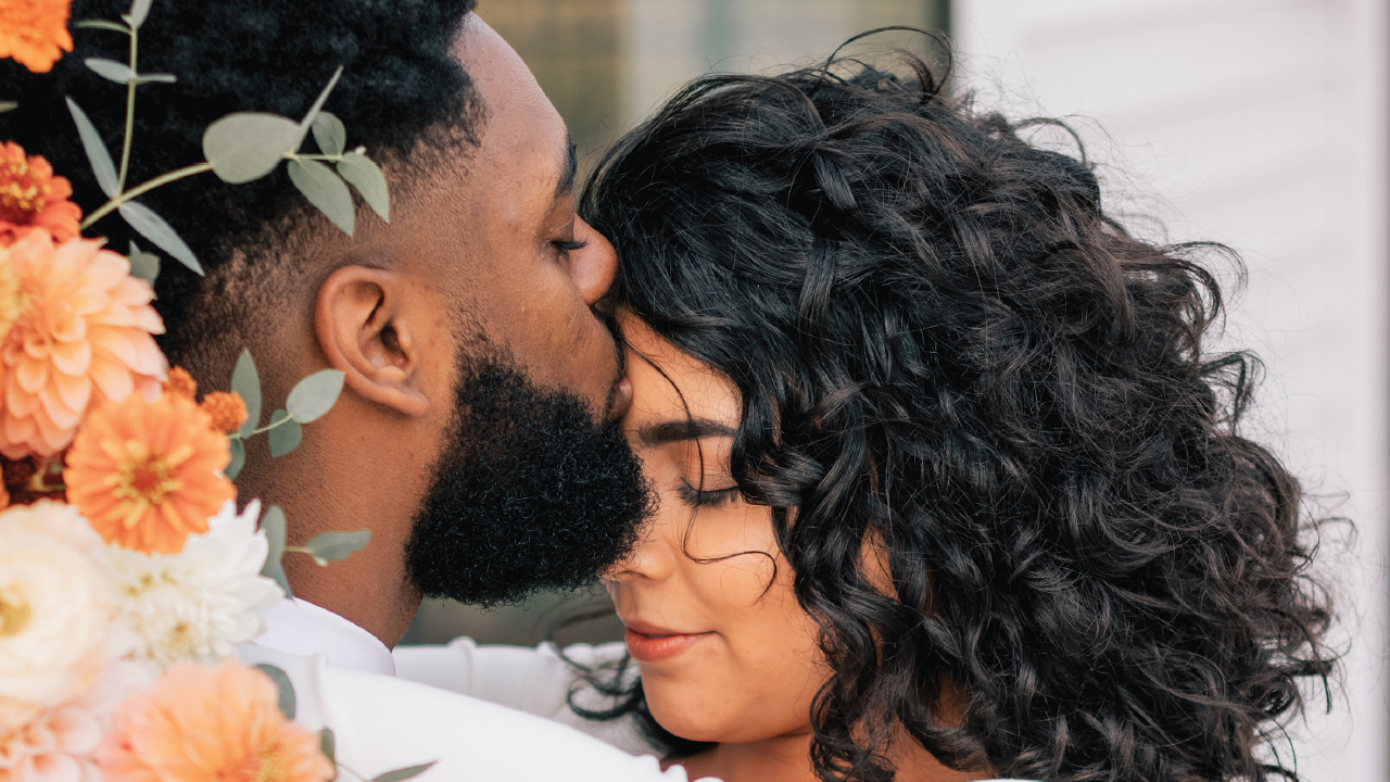Montel Caruthers kissing his fiance's forehead, Gloria Oyervides