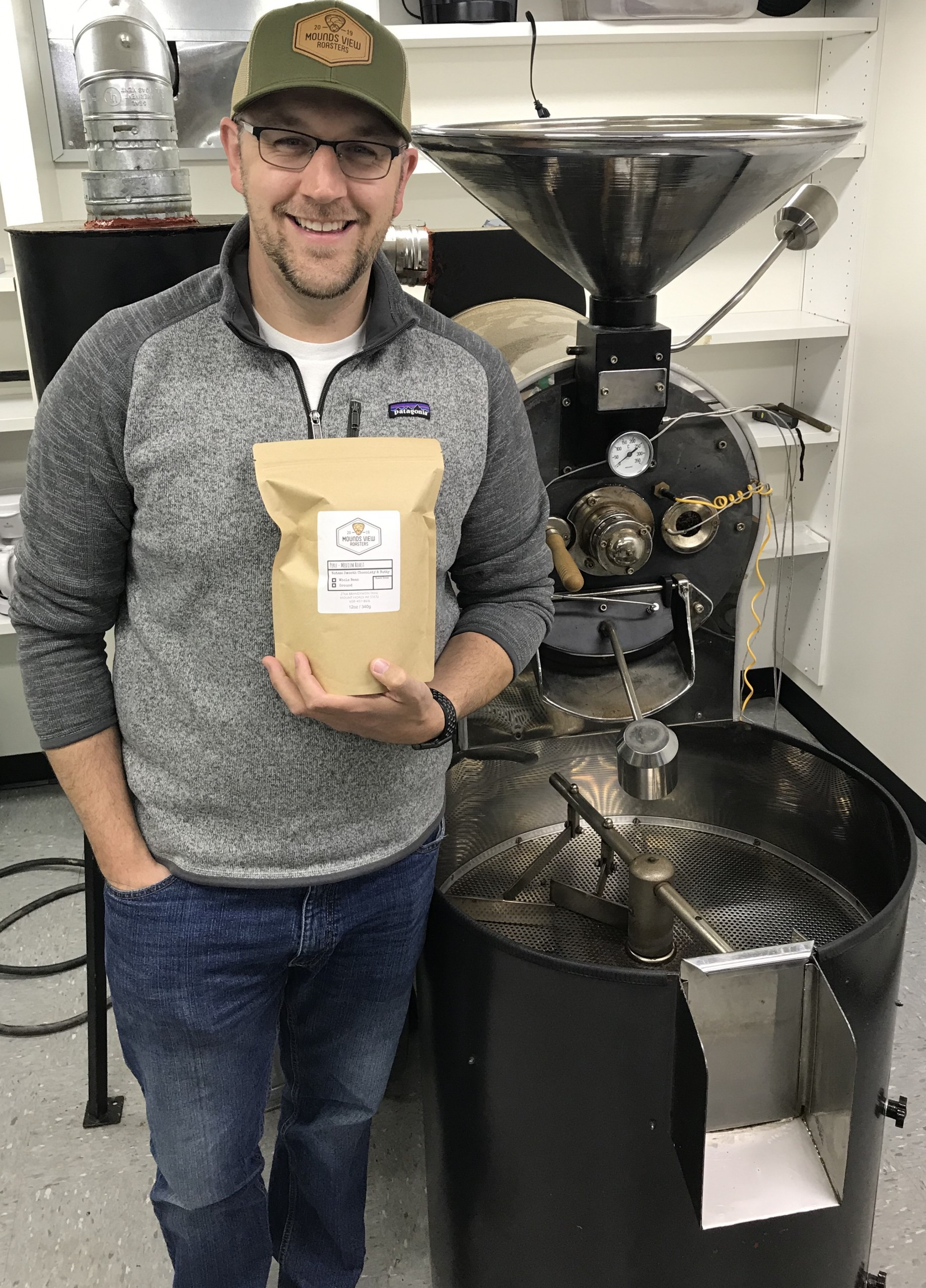Michael Cleary holding a bag of coffee in front of roaster