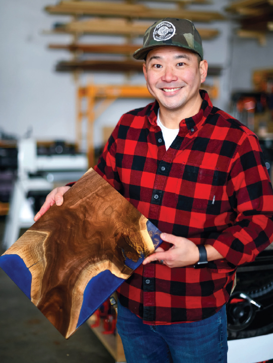Jay kang holding a piece of wood