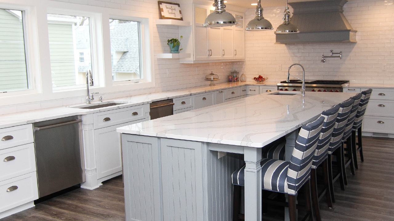 Modern Kitchen with Island countertop and striped high chairs with pendant lamps